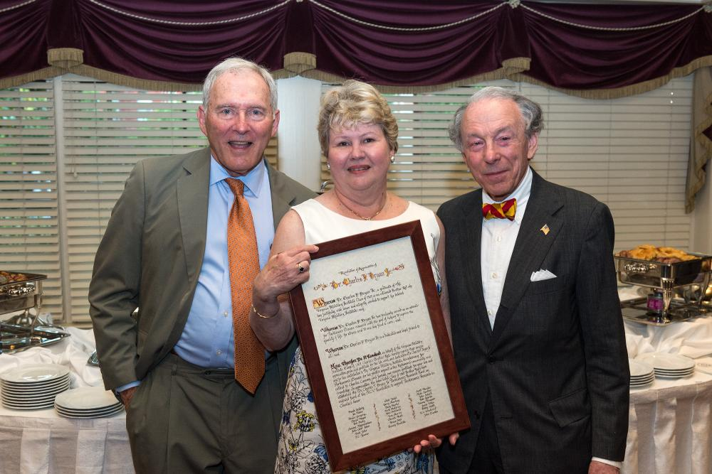Charlie Bryan and his wife Cammy Bryan, along with John Ishon, look over a resolution in appreciation of Charlie that was presented at the reception where the Dr. Charles F. Bryan Jr. Parkinson's Research Fund was announced.