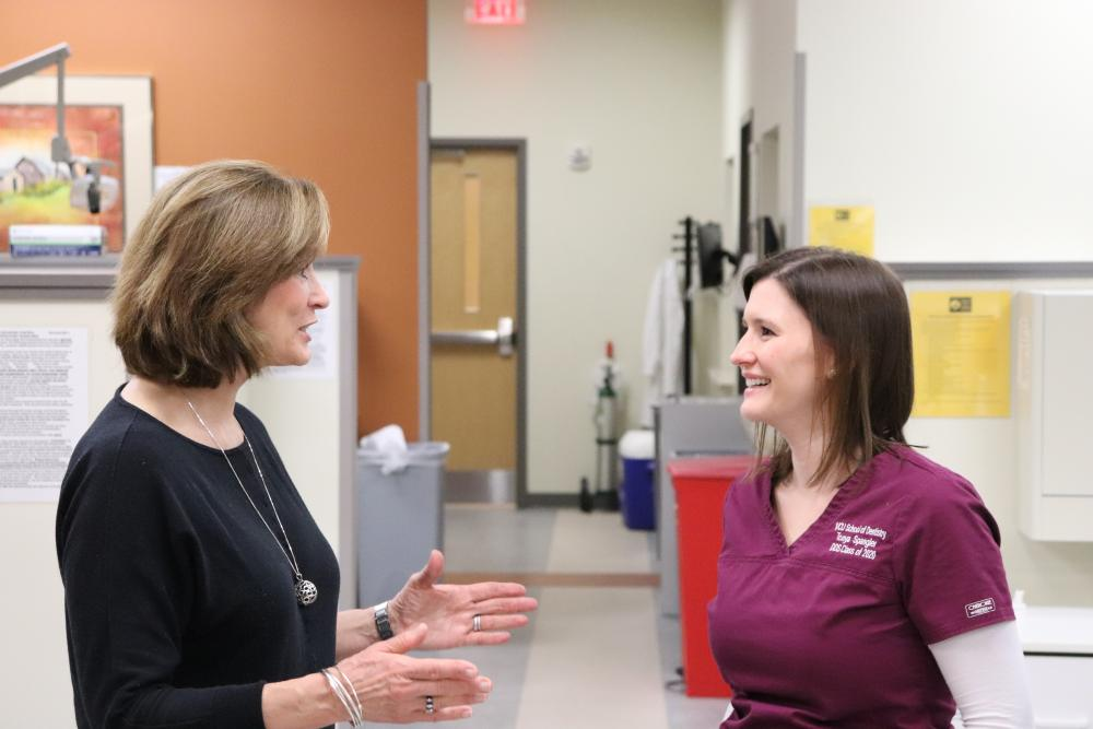 Kit Sullivan and Tonya Spangler chat in a dental clinic.