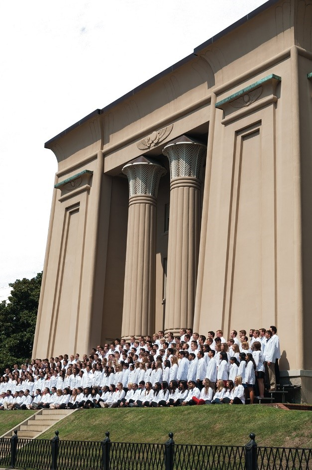 A photo captures a 21st Century VCU School of Medicine class outside of the Egyptian Building, At the time of the 1918 Influenza Pandemic, the Medical College of Virginia — the precursor to the VCU School of Medicine —   played a key role in treating Virginians and WWI soldiers. Now the school continues to foster patient care, research and education that save lives every day in our commonwealth and around the globe.