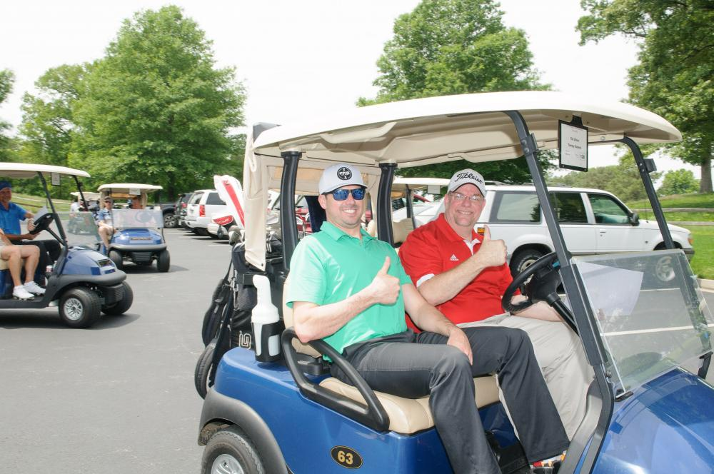 Golfers giving a thumbs-up in a golf cart